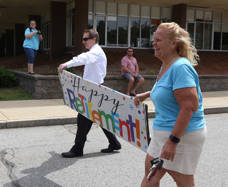 Parade for retiring Tyngsboro Middle School teacher Karen Gagnon, in front of the school. Civics teacher Keith O'Brien and Gagnon carry the banner she was given. (SUN/Julia Malakie)
