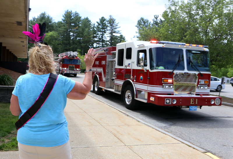 Parade for retiring Tyngsboro Middle School teacher Karen Gagnon, in front of the school. Gagnon waves as Tyngsboro fire engines drive by. She'd had some of the firefighters as students. (SUN/Julia Malakie)