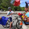 Parade for retiring Tyngsboro Middle School teacher Karen Gagnon, in front of the school. Chase Provencher, who rode his bike because he lives across the street, gives Gagnon a card, balloon and flowers. (SUN/Julia Malakie)