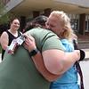 Parade for retiring Tyngsboro Middle School teacher Karen Gagnon, in front of the school. Science teacher Tilli Andrews-Wojtczak of Westford, left, hugs Gagnon as math teacher April Eringis of Lowell looks on.(SUN/Julia Malakie)