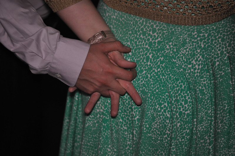 Carly and John hold hands.