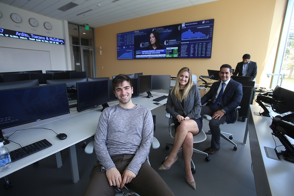 . From left, senior Dan Parravano of Waltham, sophomore Kellsie Howard of Georgetown, senior Yefry Matos of Lynn and senior Naveen Kumar of North Andover, wait for visitors to the Bloomberg Center/Trading Room, after the ribbon cutting ceremony for the Pulichino Tong Business Center, new home of the Manning School of Business at UMass Lowell. (SUN/Julia Malakie)