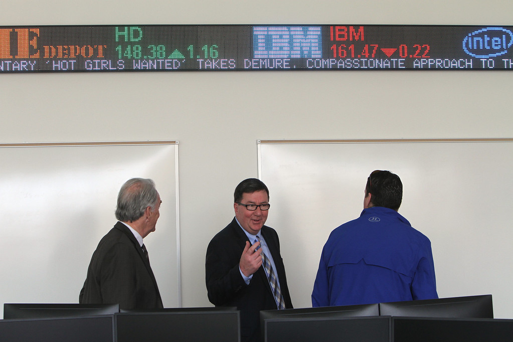 . From left, Jay Linehan, State Rep. Dave Nangle, and Manning School IT specialist Brian Donovan, tour the Bloomberg Center/Trading Room after the ribbon cutting ceremony for the Pulichino Tong Business Center, new home of the Manning School of Business at UMass Lowell. (SUN/Julia Malakie)