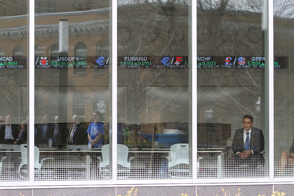 . From the Bloomberg Center/Trading Room, senior Yefry Matos of Lynn watches the ribbon cutting ceremony for the Pulichino Tong Business Center, new home of the Manning School of Business at UMass Lowell. (SUN/Julia Malakie)