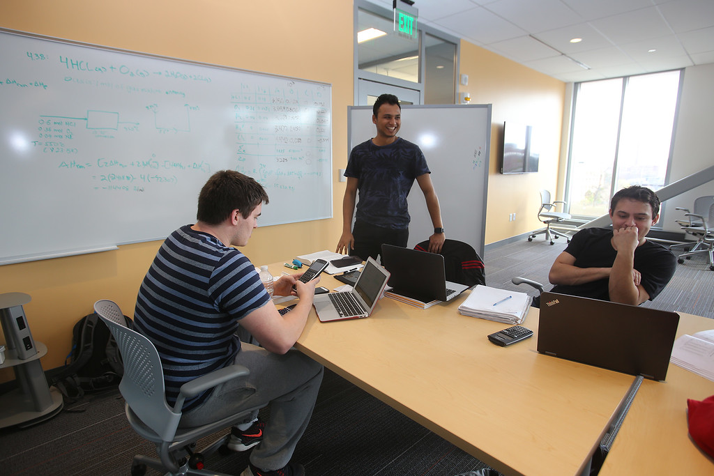 . From left, UML sophomore Fitzy Forsyth of Acton, junior Mikil Patel of Nairobi, Kenya, and Roger Garcia of Pepperell, work in one of the collaboration spaces at the Pulichino Tong Business Center, new home of the Manning School of Business at UMass Lowell. (SUN/Julia Malakie)