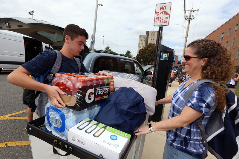 Moving-in day at UMass Lowell. Connor Pozzi, 18, of Seekonk, N.H., loads up a bin with his mother Pam Pozzi, as he moves into University Suites Residence Hall. (SUN/Julia Malakie)
