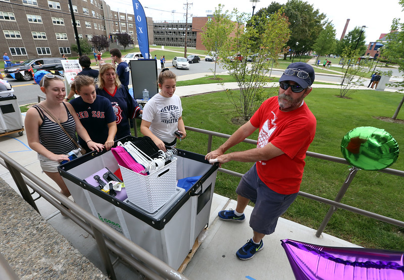 Moving-in day at UMass Lowell. Twins and incoming freshmen Madison, second from left, and Mackenzie Cunningham (white tee shirt) of Revere, move into Fox Hall with their sister, senior Morgan Cunningham, mother Debbie, rear, and father Patrick Cunningham. The twins plan to major in Math, as their older sister is doing. (SUN/Julia Malakie)