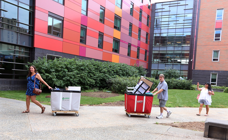 Moving-in day at UMass Lowell. Madonna McGuire, 18, of Gloucester, left, moves into University Suites with help from her mom's friend Todd Hadley of Gloucester, and her mom Lourdes Garcia, documenting the event with her phone. (SUN/Julia Malakie)