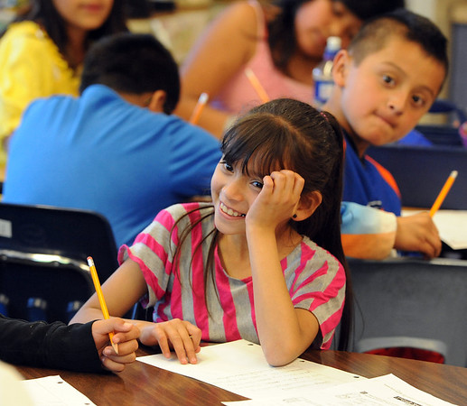 """Daisy Ordaz smiles at her classmate during class on Wednesday.<br /> All of the 3rd-graders at University Hill Elementary  who took the English version of the TCAP test scored proficient or advanced.<br /> Sunday. For more photos of 3rd-graders at Uni-Hill, go to  <a href=""""http://www.dailycamera.com"""">http://www.dailycamera.com</a>.<br /> Cliff Grassmick / May 9, 2012"""
