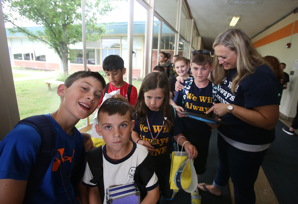 . Last day of school at Vining Elementary School before it closes. Front, from left, Justin Pappalardo, 10, and his brother Michael, 8, Isabella Allaby, and Jaden Hubis with staff member Emily Ward, as walkers wait to be called to meet their parents. (SUN/Julia Malakie)