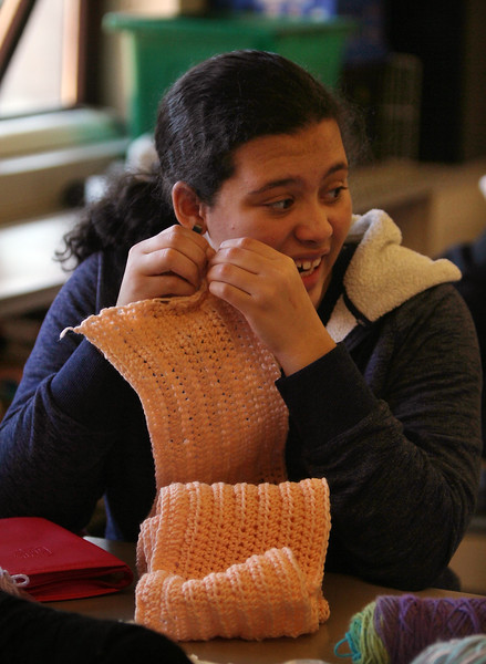 Sixth graders at Dr. An Wang Middle School knit and crochet during advisory period, making scarves and other items to donate to the Lowell Transitional Living Center. Alisse Arzuaga, 11, with her crocheted scarf. (SUN/Julia Malakie)