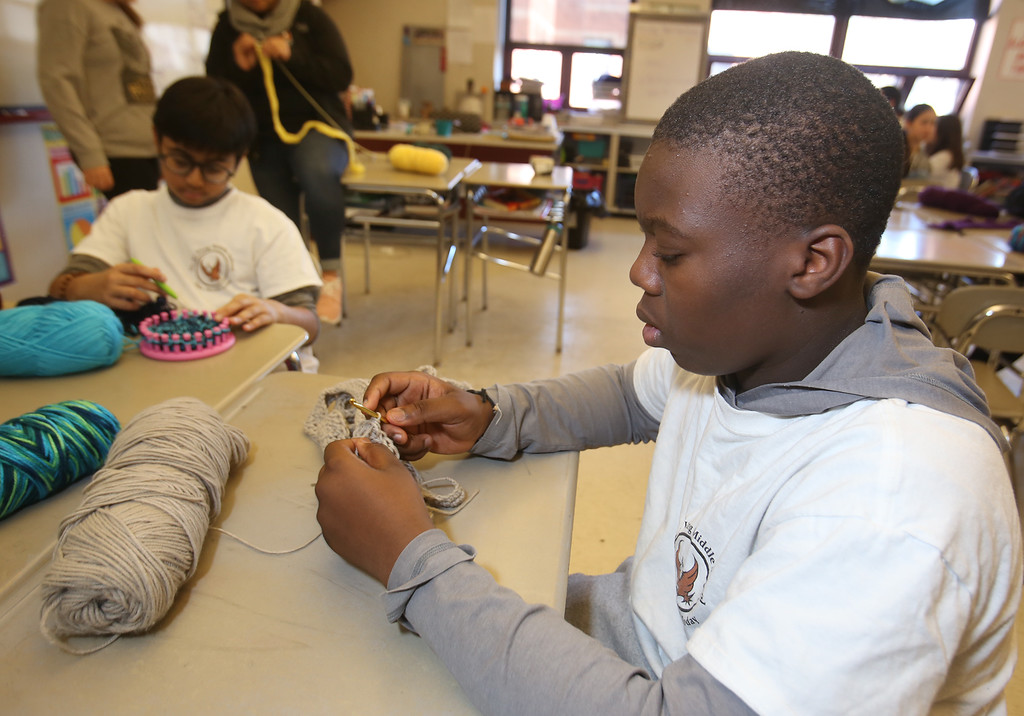. Sixth graders at Dr. An Wang Middle School knit and crochet during advisory period, making scarves and other items to donate to the Lowell Transitional Living Center. Ronald Dossa, 11, right, crocheting, and Dhruv Patel, 11, rear, using a circular knitting loom. (SUN/Julia Malakie)