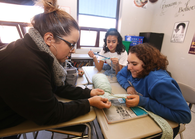 Sixth graders at Dr. An Wang Middle School knit and crochet during advisory period, making scarves and other items to donate to the Lowell Transitional Living Center. From left, 6th grade math teacher Amila Colon of Lowell, Jennielis Estrada, 12, and Alexia Medina, 11. (SUN/Julia Malakie)