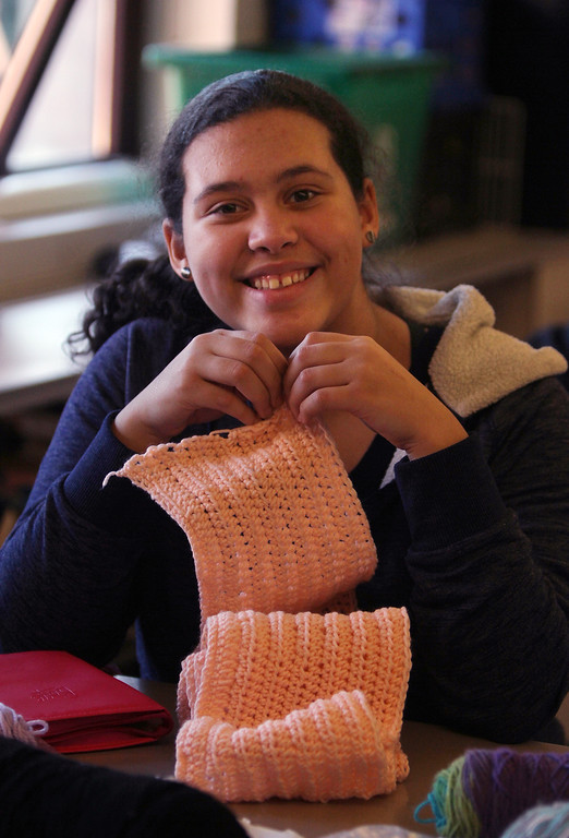 . Sixth graders at Dr. An Wang Middle School knit and crochet during advisory period, making scarves and other items to donate to the Lowell Transitional Living Center. Alisse Arzuaga, 11, with her crocheted scarf. (SUN/Julia Malakie)