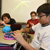 Sixth graders at Dr. An Wang Middle School knit and crochet during advisory period, making scarves and other items to donate to the Lowell Transitional Living Center. From left, Chase Ziemba, 12, and Luis Bodon, 11, crocheting, and Dhruv Patel, 11, using a circular knitting loom. (SUN/Julia Malakie)