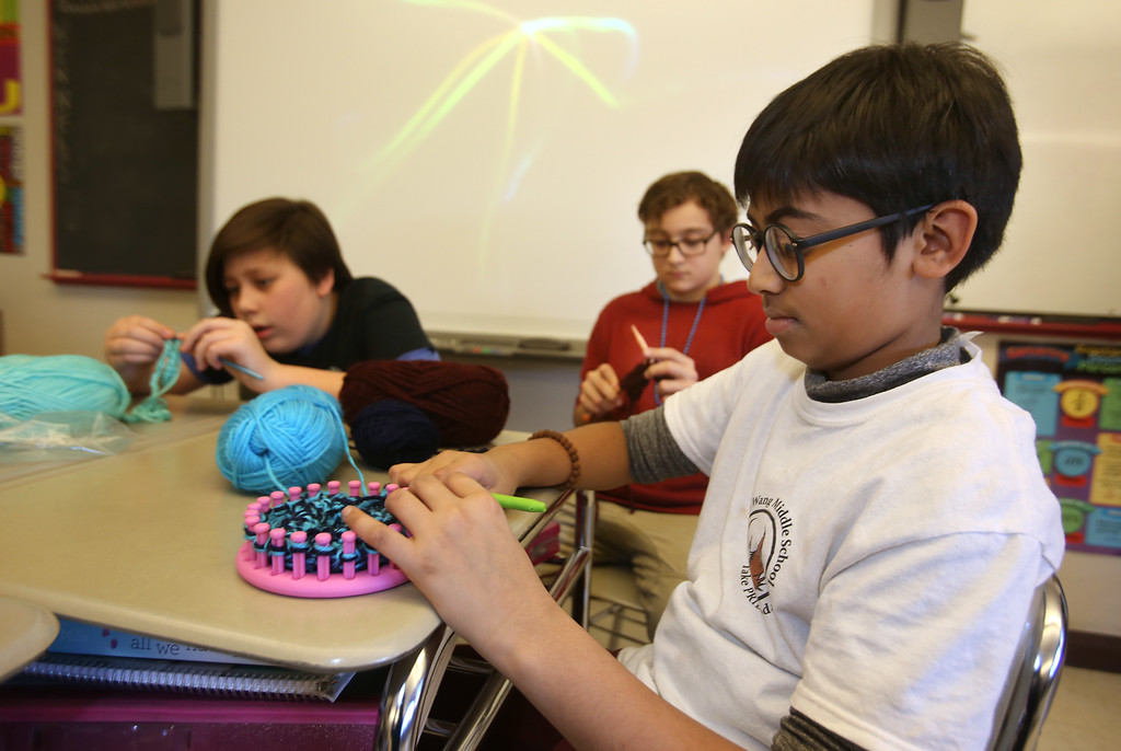 . Sixth graders at Dr. An Wang Middle School knit and crochet during advisory period, making scarves and other items to donate to the Lowell Transitional Living Center. From left, Chase Ziemba, 12, and Luis Bodon, 11, crocheting, and Dhruv Patel, 11, using a circular knitting loom. (SUN/Julia Malakie)