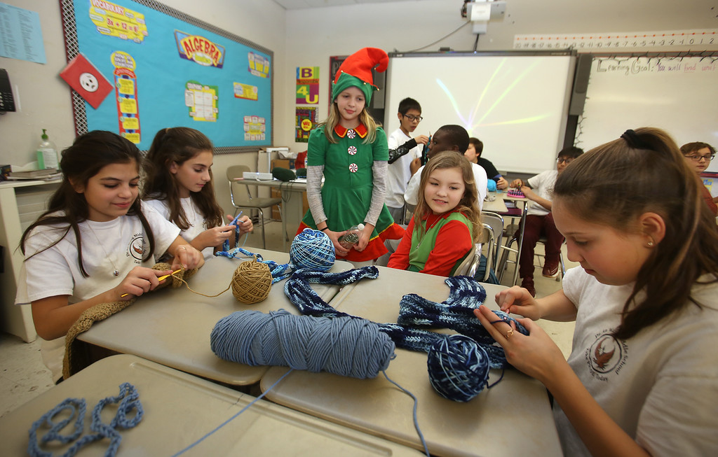 . Sixth graders at Dr. An Wang Middle School knit and crochet during advisory period, making scarves and other items to donate to the Lowell Transitional Living Center. From left, Alexia Cote, 11, Stefanie Grillakis, 11, 5th graders Kaylee Tousignant, 11, and Samantha Brady, 10, who are in the Elf musical, and Lilyanna Nieves, 11. (SUN/Julia Malakie)
