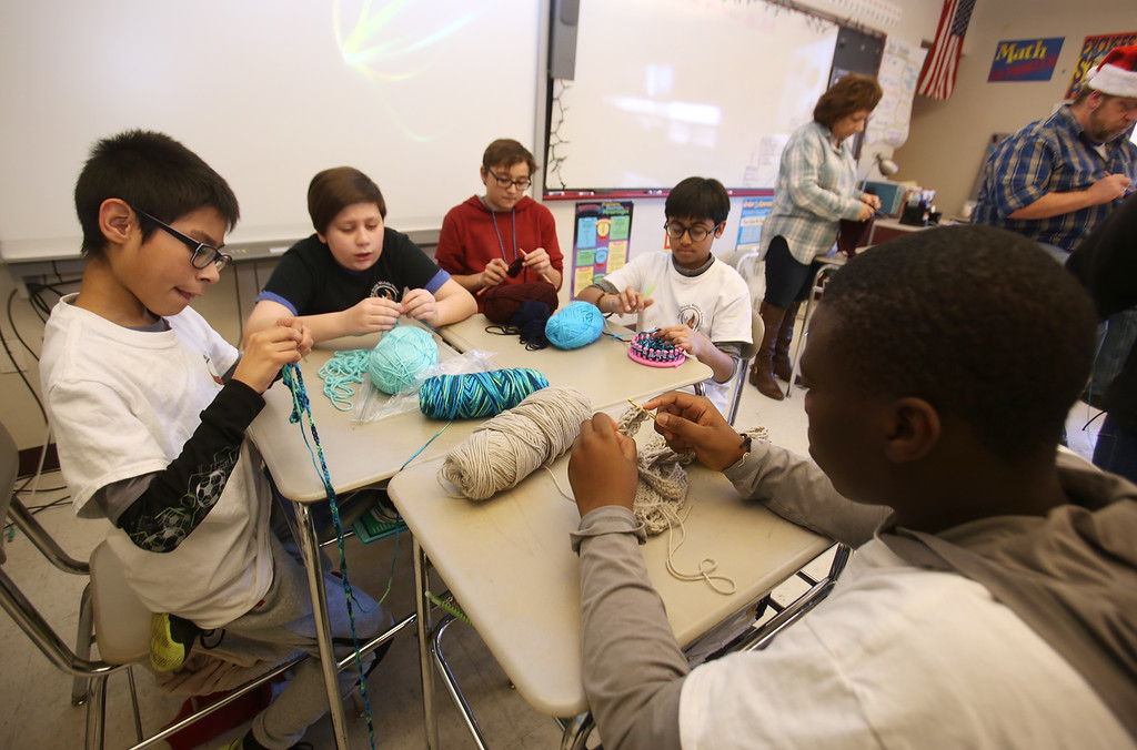 . Sixth graders at Dr. An Wang Middle School knit and crochet during advisory period, making scarves and other items to donate to the Lowell Transitional Living Center. From left, Brandon Rivas, 11, Chase Ziemba, 12, Luis Bodon, 11, Dhruv Patel, 11, and Ronald Dossa, 11. (SUN/Julia Malakie)