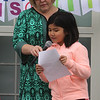 Washington Elementary School in Lowell holds a celebration for their new Peace Garden. Principal Cheryl Cunningham holds the microphone as 4th grader Sophal Yan leads a peace pledge.  (SUN/Julia Malakie)