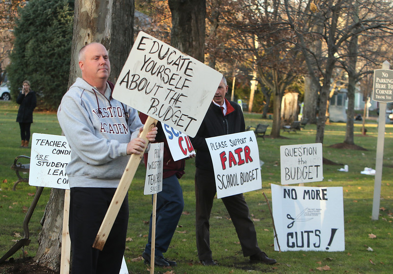 Members of Westford Education Association, the teachers' union, hold signs at Town Common to protest expected school budget cuts. Dave DeLong of Woburn, who teaches math at Westford Academy. At right is WA social studies teacher Chris Connole of Auburn. (SUN/Julia Malakie)