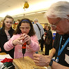 Wilmington Middle School science & technology fair sponsored by Analog Devices, Inc. From left, 7th graders Maya Mulas and Juliana Ragucci, both 12, try out a cordless power screwdriver under supervision of Doug Mercer of Bradford, a consulting fellow at Analog. (SUN/Julia Malakie)