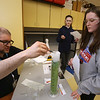 Wilmington Middle School science & technology fair sponsored by Analog Devices, Inc. Analog Devices customer quality engineer Josh Libby of Medford adds some powdered detergent to make the water change color, at the dry ice station, as 7th graders Juliana Angiuoni, 12, right, and Keira Rice, 12, watch. (SUN/Julia Malakie)