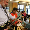 Wilmington Middle School science & technology fair sponsored by Analog Devices, Inc. Retired applications engineer Jonathan Pearson of Topsfield show 7th grader Arian Urena, 13, an oscilloscope while playing guitar. (SUN/Julia Malakie)