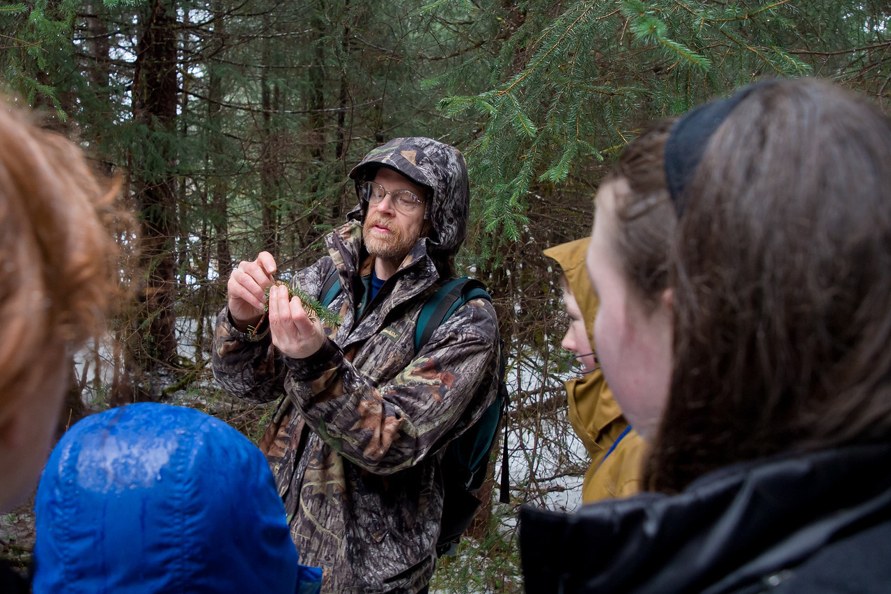 Richard shows students a branch that a pocupine had chewed through.