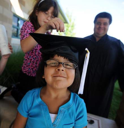 "Holley Pinley tries on her dad's graduation cap, as sister Samantha and father Bobbie look on.<br /> Workforce Boulder County held its Summer 2010 GED graduation on Friday at the Izaak Walton Clubhouse in Longmont.<br /> For more photos of the graduation, go to  <a href=""http://www.dailycamera.com"">http://www.dailycamera.com</a>.<br /> Cliff Grassmick / August 20, 2010"