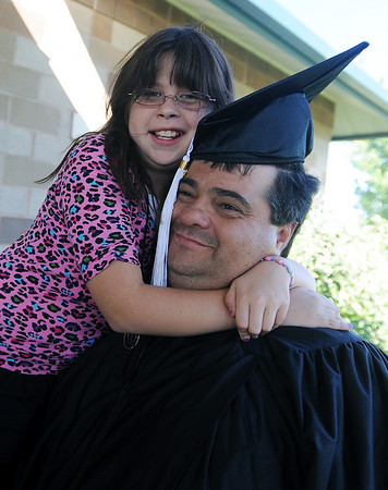 "Samantha Pinley has a hug for her graduating father, Bobbie.<br /> Workforce Boulder County held its Summer 2010 GED graduation on Friday at the Izaak Walton Clubhouse in Longmont.<br /> For more photos of the graduation, go to  <a href=""http://www.dailycamera.com"">http://www.dailycamera.com</a>.<br /> Cliff Grassmick / August 20, 2010"