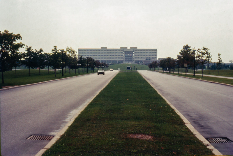 York University. Looking towards the Ross Building from near Keele Street. Signs along left lane are for hitchhiking destinations. Mound in front of Ross Building. 1971