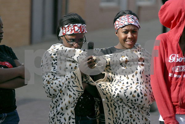 -Messenger photo by Hans Madsen<br /> <br /> Breonnah Al-Hameed, left, carefully records the passing Fort Dodge Senior High School homecoming parade with her cell phone camera Friday afternoon while sharing a warm blanket in the cool weather with her friend Arianna Newsome.