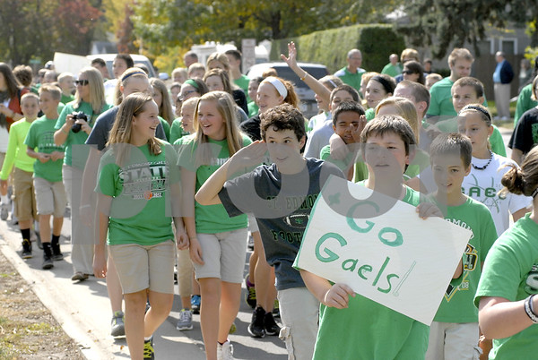 -Messenger photo by Hans Madsen<br /> <br /> Hand to ear, Jake Rossow encourages his fellow students along the sidewalk to give a rousing cheer for the Gaels Friday afternoon as he walks in the school's annual Homecoming spirit parade.