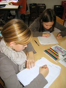 Yentl en Emma zijn heel geconcentreerd aan het werken aan hun eigen strip.