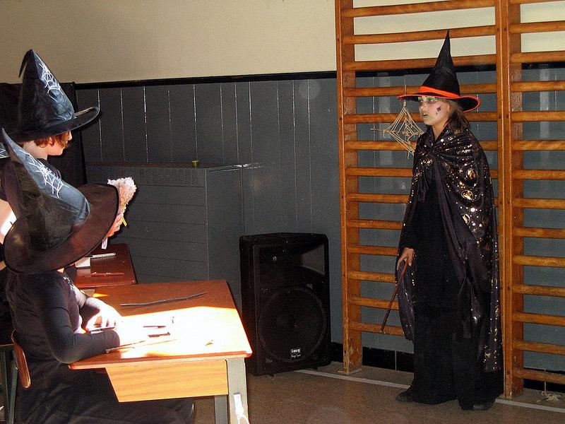 De meestertovenaar komt binnen terwijl de klas op stelten wordt gezet.