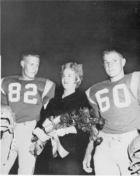 A very happy Alethea Turner, 1960 Football Queen, Smiles on all the surroundin football players who stood at attention ss she walked across the field escorted by team captains, Bill Perr and Donnie Williams.