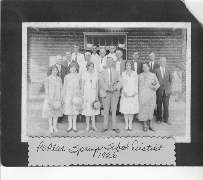"1926 Poplar Springs Consolidated School opening.  Inscription on building reads ""Poplar Springs School District, Minerva Academy. Trustees: A. J. Guthrie, Chairman, J. L. Hughes, Secretary and Treasurer, N. L. Singletary; Originators of Consolidation, Moses G. Sirmons, S. M. Green, Dr. J. R. Lasseter; William G. Avera, Designer of Building, W. E. Register, Builder 1926."" Teachers, Annie Lee Nix Maddox, Golie Spells, _____Sike, Charlie E. Parham, Alice Knight.  (It is thought that many of the above-named persons are in this photo; Wm (Bill) G. Avera, School Superintendent, is the man with left hand against his chest, near middle of 2nd row.)"