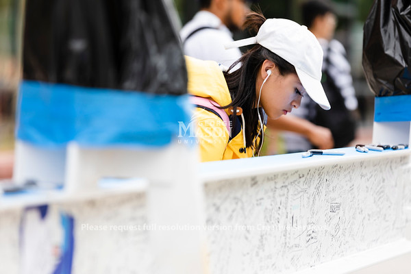People sign a beam that will be used in the construction of a new academic building as part of the Core Campus Project. Photo by Lathan Goumas/Office of Communications and Marketing   Photo Taken:Wednesday, August 28, 2019
