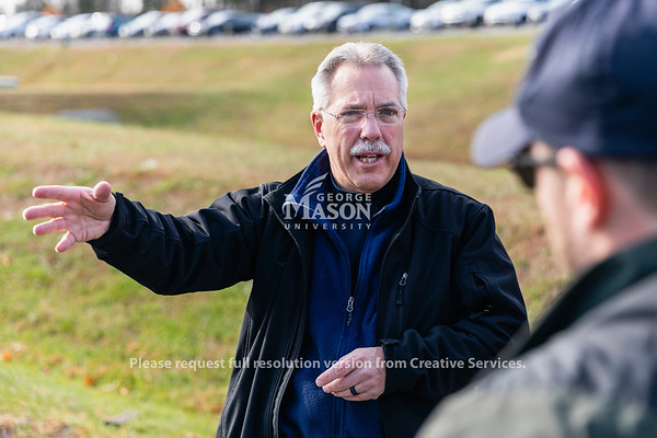 Professor Steven Burmeister talks with a member of the Fairfax City Police about a mock car accident during a training for a 3-dimensional scanning system know as FARO 3D. Photo by Lathan Goumas/Office of Communications and Marketing   Photo Taken:Tuesday, November 19, 2019