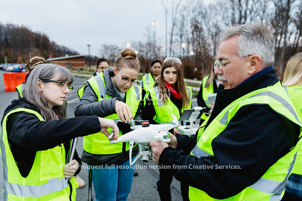 Professor Steven Burmeister shows an unmanned arial vehicle to students in his FRSC 516 Forensic Drone Photography class. Photo by Lathan Goumas/Office of Communications and Marketing   Photo Taken:Tuesday, November 19, 2019