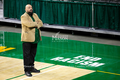 """Dr. Michael Nickens (a.k.a. Doc Nix) stands by the """"End Racism"""" sign on the court at EagleBank Arena. Photo by: Shelby Burgess/Strategic Communications/George Mason University"""