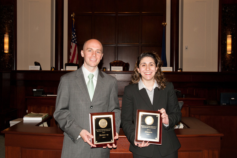 """Law School students and """"defendant"""" Timothy Cronin and """"plaintiff"""" Azadeh Malek hold their plaques after they competed in the Law School's final round of the First Year Moot Court Competition at US District Court, Eastern District of Virginia, in Alexandria. Photo by Alexis Glenn/Creative Services/George Mason University"""
