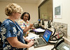 Professors Beverly Middle (L) and Sonya Almond monitor CHHS Nursing students working in the Simulation Lab at Fairfax Campus. Photo by Alexis Glenn/Creative Services/George Mason University