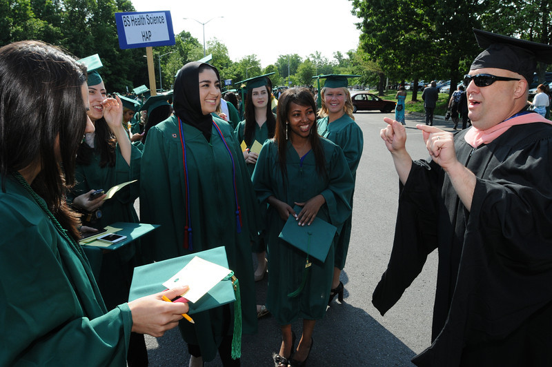 Assistant Professor Andrew Carle congratulates students at the College of Health and Human Services Convocation 2012. Photo by Evan Cantwell/Creative Services/George Mason University