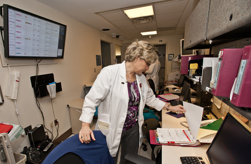 Prof. Beverly Middle, RN, MSN, School of Nursing, CHHS, and PhD student, checks a patient's chart as she shadows Dierdre Carolan on her daily rounds at Inova Hospital in Fairfax. Photo by Alexis Glenn/Creative Services/George Mason University