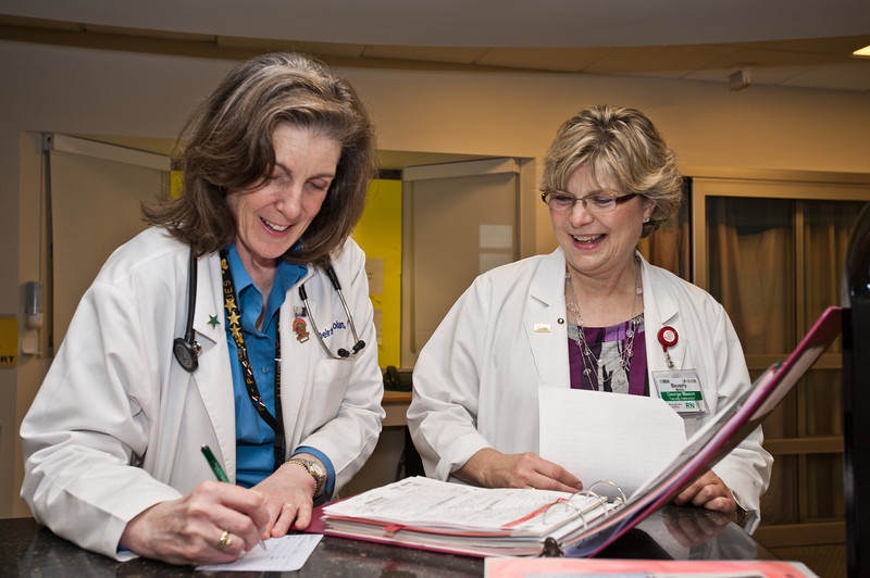 Prof. Beverly Middle (R), RN, MSN, School of Nursing, CHHS, and PhD student, shadows Dierdre Carolan on her daily rounds at Inova Hospital in Fairfax. Photo by Alexis Glenn/Creative Services/George Mason University