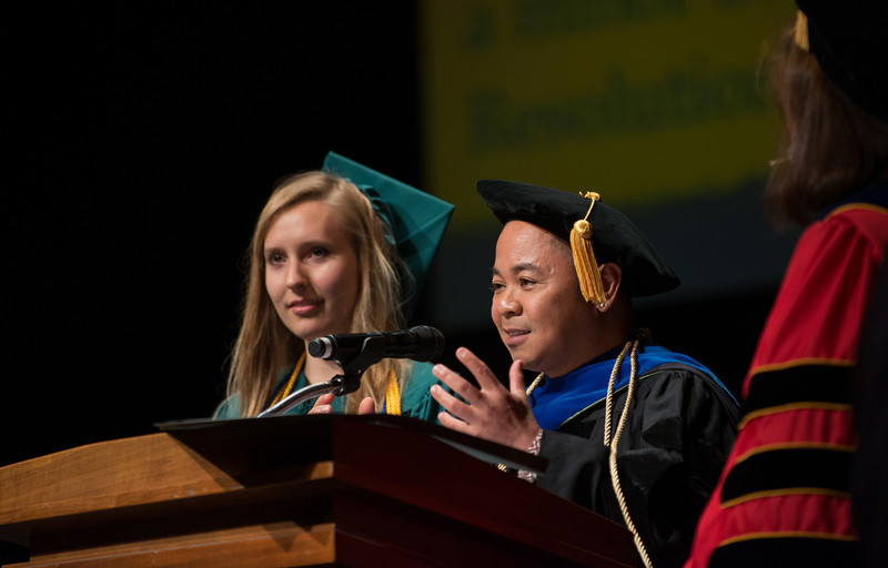 Al Fuertes, Assistant Professor, announces an outstanding graduate award recipient Lela Ross during the New Century College Convocation. Photo by Evan Cantwell/Creative Services/George Mason University