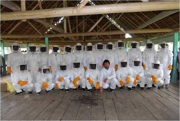 The beekeepers in their protective gear. Perilla is uncovered as a way to show the new beekeepers not to be afraid. Provided by German Perilla.