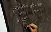 A University Physics student solves a problem on the blackboard during class at Fairfax Campus. Photo by Alexis Glenn/Creative Services/George Mason University