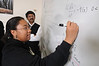 Mathematics faculty, Padhu Seshaiyer, works with students on equations at the white board.  Photo by Evan Cantwell/Creative Services/George Mason University